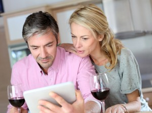 Couple drinking wine while looking at an Ipad