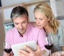 Couple-drinking-wine-while-looking-at-an-Ipad