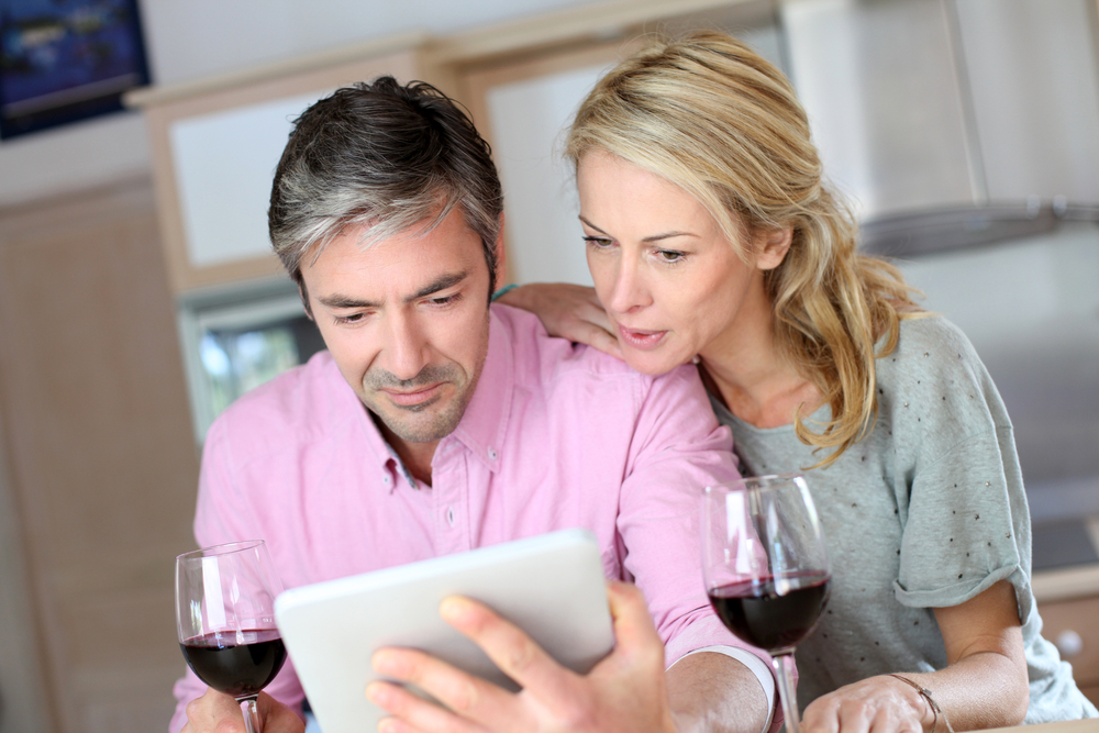 Couple drinking wine while looking at an Ipad - Getting some closure