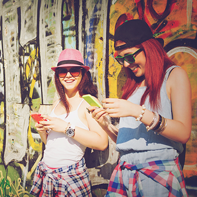 Two teenage girls with smartphones - Portrait of a new American wine drinker